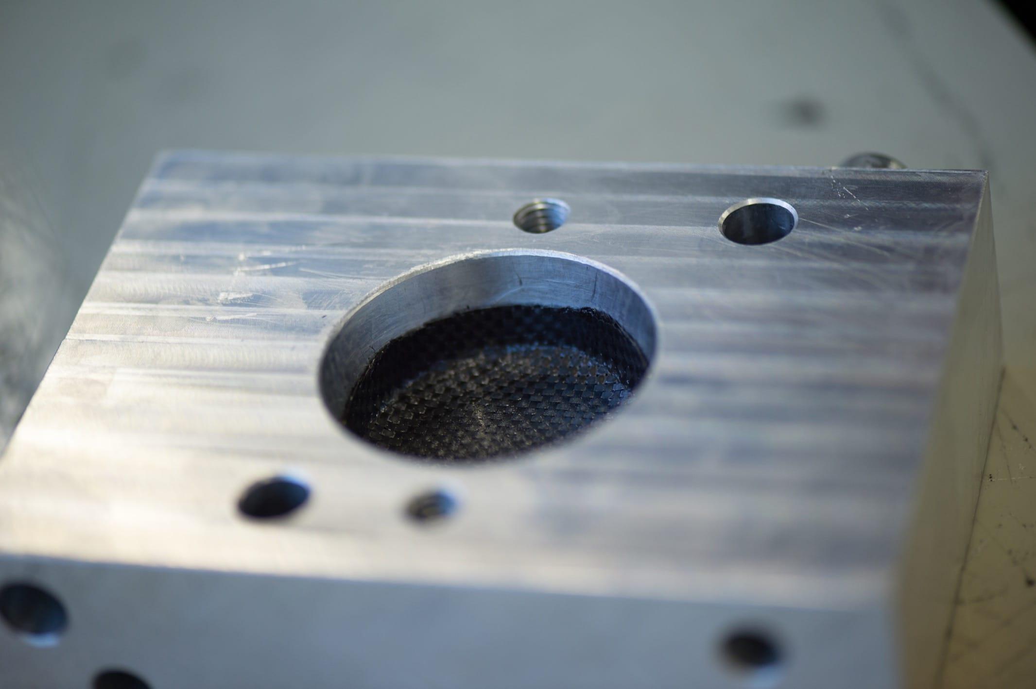 Erste Schicht Prepreg-Karbongewebe, in die Negativpressform der Lünette eingelegt.